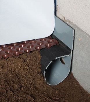 Closeup of a crawl space drainage system installed in Skowhegan