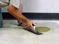 Repairing the cored holes in the concrete slab floor with fresh concrete and cleaning up the Auburn home.