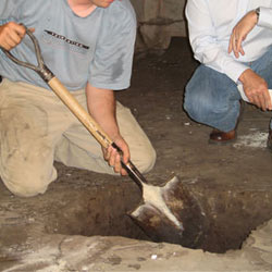 Digging a hole for the engineered fill used in a crawl space support system installation in Waterville