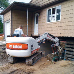Excavating to expose the foundation walls and footings for a replacement job in Brunswick