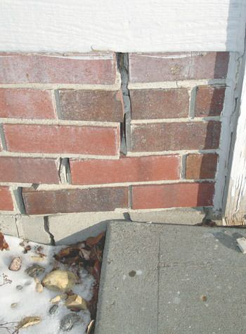 Severe street creep damage to a garage wall outside a Old Town home