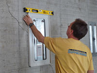 Positioning a wall plate cover on a foundation wall in Waterville.