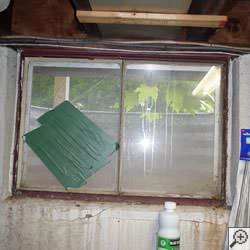 An old, rusted basement window with a steel frame in Waterville.